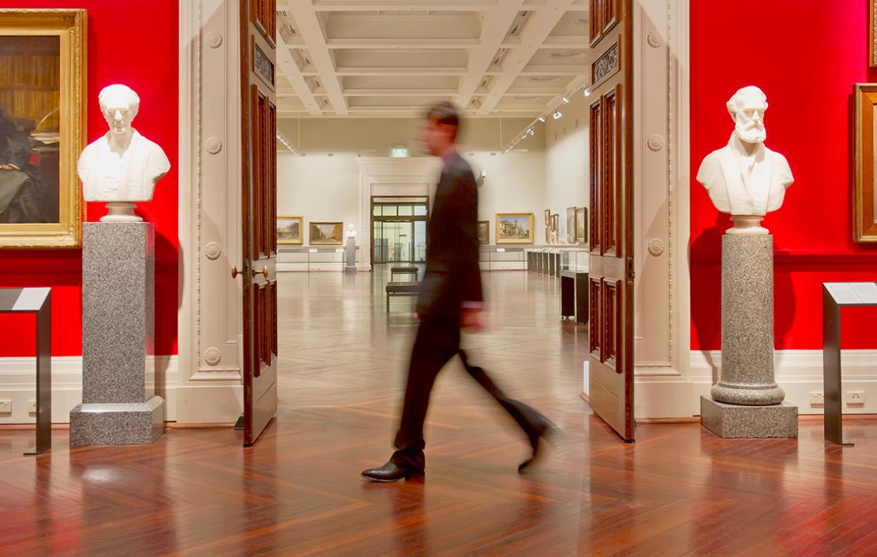Photo of a man walking through a museum exhibit.