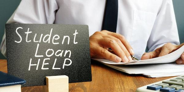 """A sign reading """"Student Loan Help"""" in front of a person looking at paperwork."""